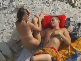 Secret fingering on the beach with a couple