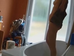 Girl in the bathroom sponging her body