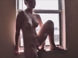 Slim girl masturbating by the window