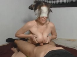 Blindfolded girl jerks off a dick with her tits