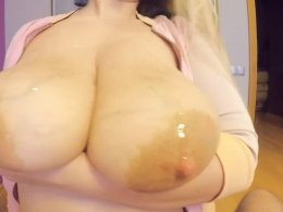 Busty chick jerks a long dong with her tits