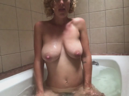 Busty girl films her tits in the bathtub