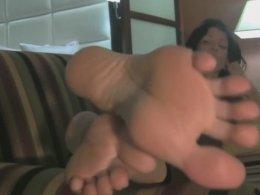 Kinky brunette girl films her feet