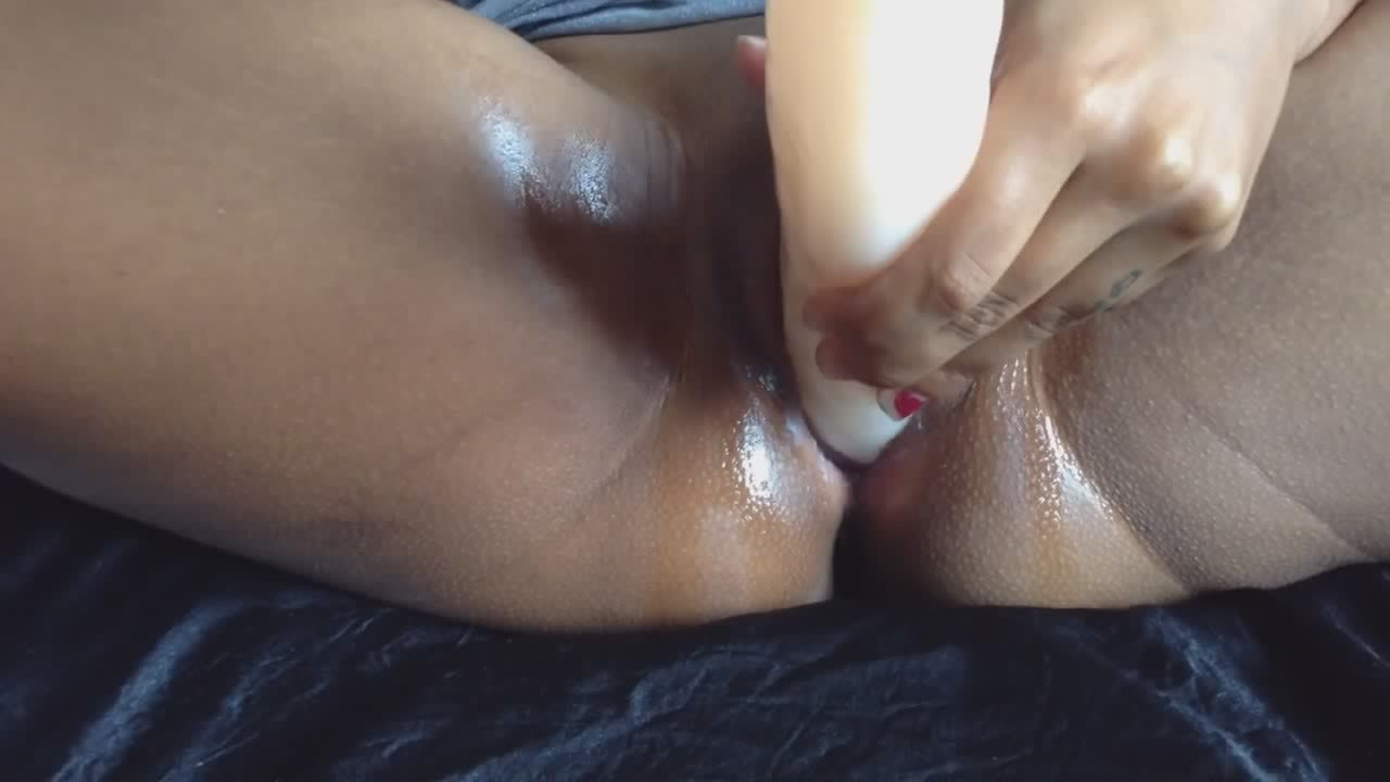 Oiled Up Ebony Fills Her Tunnel With A Long Dildo